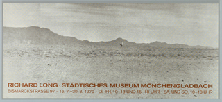 Art exhibition poster showing a black and white photo of a person standing in the desert with a mountain range in the distance on the horizon.  The text is printed in brown along the bottom.  The sheet is an oblong horizontal to emphasize the panoramic view of the landscape.