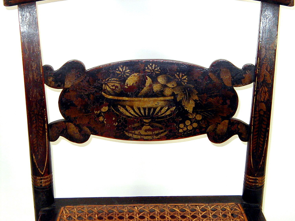 "Rolled pillow back and front seat rail; so-called ""turtle"" slat stencilled with design of footed bowl of fruits.  Turned straight front legs on button feet.  Four lateral and two longitudinal turned stretchers.  Caned seat.  Gilt bandings on black ground."