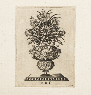Vertical rectangle showing a vase with three fantastic masks containing a symmetrical floral arrangement. The vase stand on a table with gadrooning.