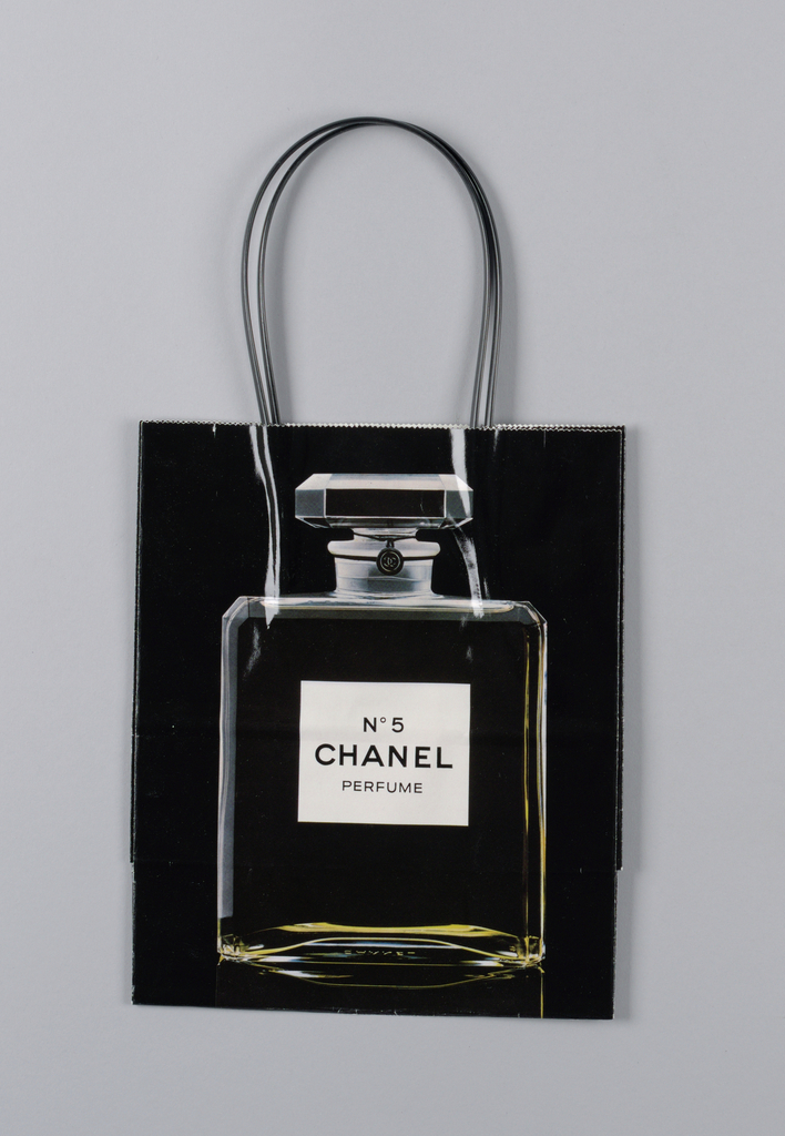 Black bag with  picture of perfume bottle at center. On base: 1979-The Chanel Classic Bottle.