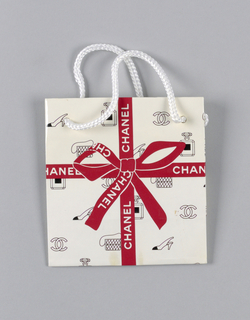 "White with red ribbon motif and illustration of bags, shoes, etc. in grid form. Small format. On base: ""Chanel, the Classic Bottle."""