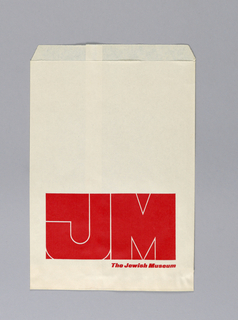 "White shopping bag with the Jewish Museum graphic identity ""JM"" outlined in white within red horizontal rectangle at bottom, red printed text below. No handles."