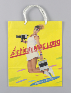 Yellow bag with photo of jumping girl in white tennis dress.  She holds video camera in right hand and  music box in left hand. Text in Asian characters in white inside blue oval in lower right corner.  Side panels: Asian text in red on white.