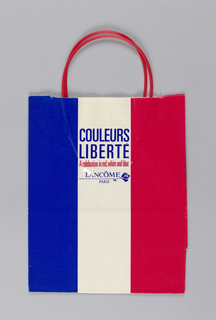 Glossy red, white and blue stripes evoking French flag, with cosmetic brand name and logo in center on white stripe. Side panels: White stars on red in one panels, blue in other.
