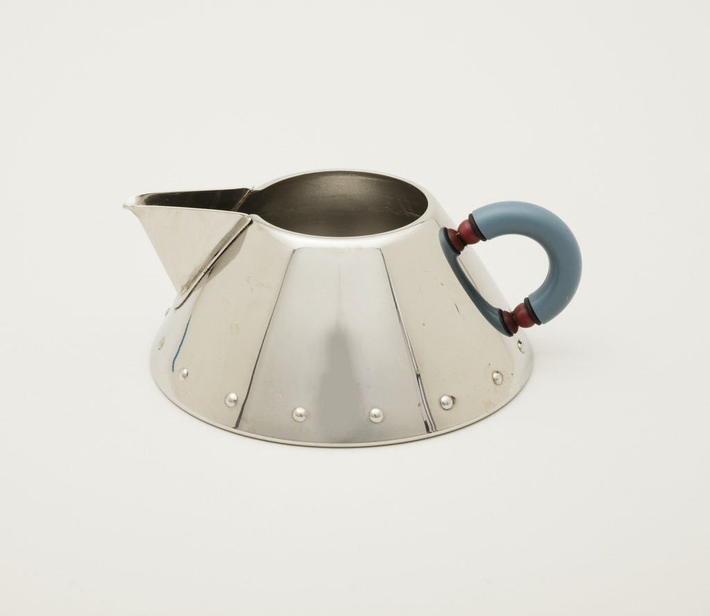 Conical form with spout and harp handle covered with blue rubber.