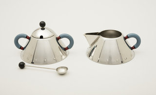 Conical sugar bowl with two blue plastic harp handles with red accents; domed lid with black plastic ball knop. Stainless steel spoon with hemispherical bowl on thin shaft handle with black plastic ball terminal.