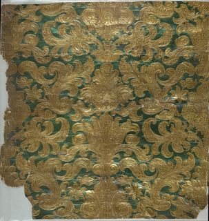 Imitation leather. Embossed, symmetrical rococo foliate pattern; printed in metallic gold and blue-green.
