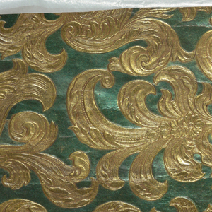 Embossed, symmetrical rococo foliate pattern; printed in metallic gold and blue-green.