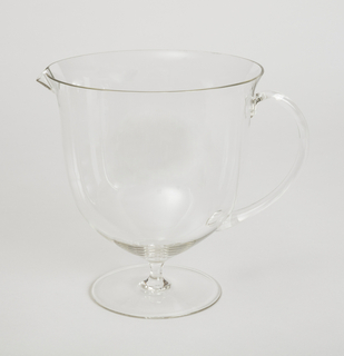 Clear, thin-walled glass form: slightly ovoid bowl with everted rim and small lip, surmounting short slender stem with slightly domed foot; large C-shaped handle.handle.