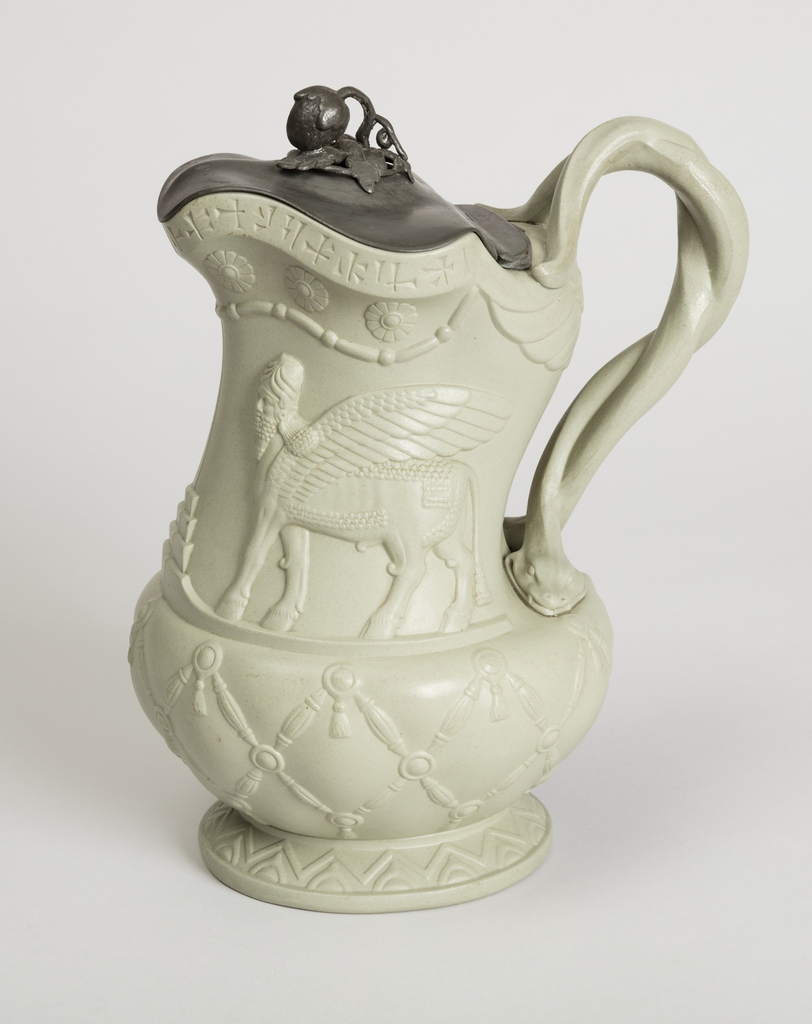 Jug with spreading foot and twisted handle in the form of a snake. Molded relief decoration showing Assyrian lamassu. Cuneiform below lip. Metal lid with floral knob.