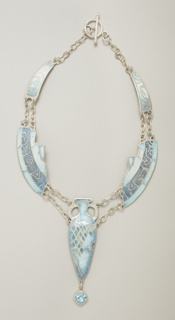 Flexible form composed of five silver elements enameled in shades of blue and connected by short double chain segments. The central element in the shape of a two-handled urn with blue detailing, and from wich depends a lozenge-shaped blue topaz in silver mount; the four side elements resemble arc-shaped shards of pottery with blue detailing remeniscient of Arabic caligraphy.