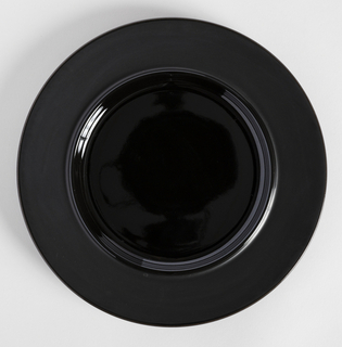 Black circular plate; high foot ring on underside.  Wide border in mat black with gloss edge ring; center concave with gloss glaze.  Gloss glazed underside, white unglazed foot ring.