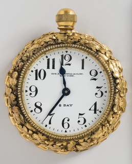 Round desk clock; case has a border of overlapping oak leaves and acorns above ribbon-tied cord and a beaded bezel