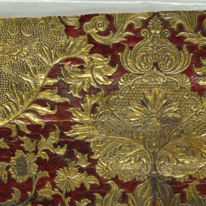 Embossed symmetrical design consisting of baroque pattern containing naturalistic floral shapes, cornucopia, acanthus leaves; printed in metallic gold and dark red.
