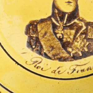 "Circular form with magenta decoration on yellow ground; portrait image of Charles X,  ""Roi de France"" in center; rim with band of foliate decoration."