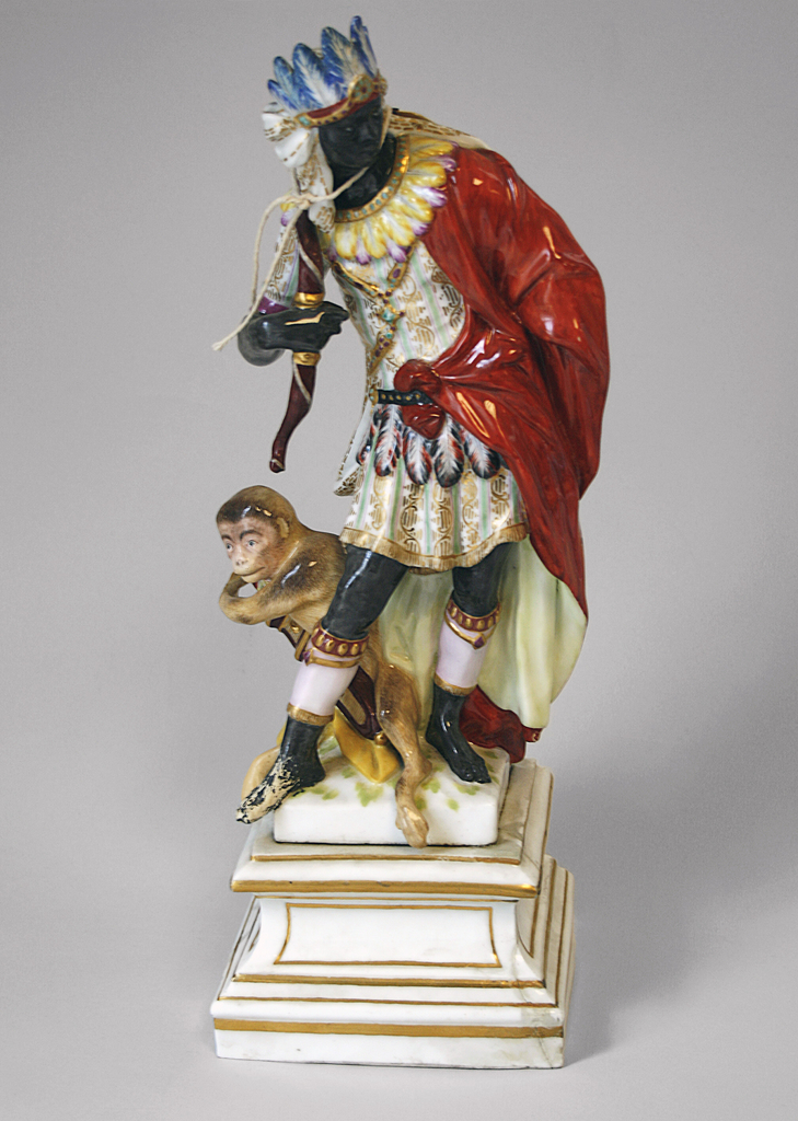 """"""" Africa"""" standing male figure, black, wearing tunic with feather belt and collar, and feather headdress, and holding bow: attended by monkey, holding quiver with arrows; square pedestal."""