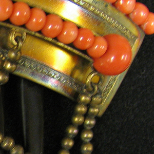 Tortoise shell comb with seven teeth and a hinged plate ornamented with two rows of coral beads and three coral pendants on chains of gold beads attached to the plate.