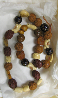 String of ojime beads, composed of 8 ivory beads in animal shapes, 4 babies, 2 beads of bone, 2 yellow moulded with masks, 8 light brown, 5 dark brown with moulded relief, 6 in guri lacquer