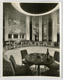 Photograph depicting the Persian Room at the Plaza Hotel in New York in its first interior design scheme. A square room with a circular wooden floor at center mirroring a two-toned circular ceiling treatment above. Highly reflective ceiling. Dark round tables with concentric contrasting stripes fill the room, each with groups of four chairs. The table in the foreground filled with etched gimlet and water glasses, a bottle of whiskey, and an ash tray. A long bar in the corner with bottles and glasses; walls draped in striped curtains. Above, a large mural depicting figural scenes of Persian musicians and dancers in fanciful landscapes. To the right, a smaller mural showing Persian princes on horseback.