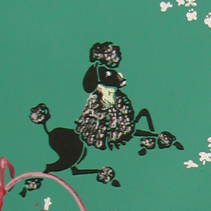 Two poodles, one black the other white, are jumping through a pink hoop, while a gray poodle frolics near a pink ribbon swarming with butterflies, and a white poodle sits and smells the flowers. A partial floral garland is shown above. Printed in colors on a dark green ground.