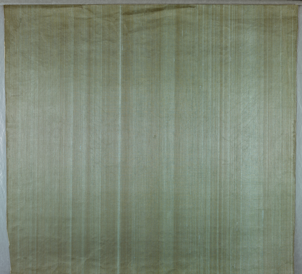 Thin pale blue silk on gray paper with a strie or stripe pattern. Textural irregularities.
