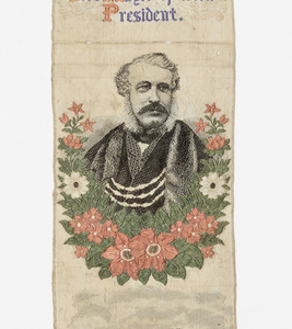 """Bookmark woven to show commemorative pictures, inscriptions. Top to bottom: a coat of arms of York; large building topped with flags, inscription """"Yorkshire Fine Arts and Industrial Exhibition opened July 1866 Rt. Hon. James Meek Lord Mayor of York, President"""", garlanded portrait of a man, Roman ruins, and the inscription: """"MULTANGULAR TOWER Each ivi'd arch and pillar lone, plead haughtily for glories gone."""" At bottom, heart-shaped motif with floral accents in red and blue. Colors: black, grey, orange, purple, green, on white ground."""