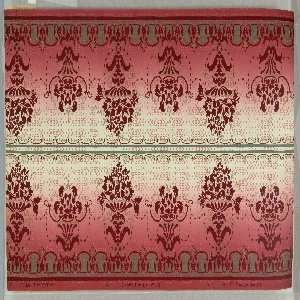 Motifs having the appearance of floral bouquet in urns, altrnating large and small. A band of green along bottom edge. Printed in burgundy, tan and green on background that shades from tan to deep red. Printed two across.