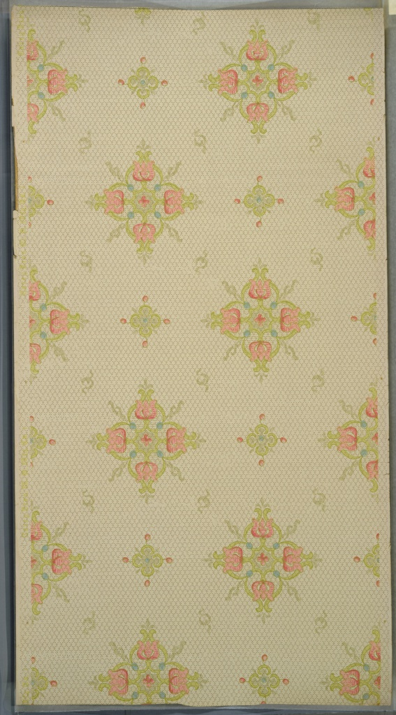 """Art nouveau style. Alternating large and small floral medallions (of stylized tulips) and S-scrolls. Background of hexagonal dot grid. Cream ground. Printed in light green, light pink, light blue and grey. Printed in selvedge: """"Carey Bros. W. P. Mfg. Co.""""  """"I"""""""
