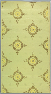 Foliate wreaths with crossed ribbons at four opposite points, with each continuing into a ribbon projection, circle in a strung bead circle centered within. Alternating secondary motifs form a faint grid pattern. Printed in metallic gold and yellow on light green ground.