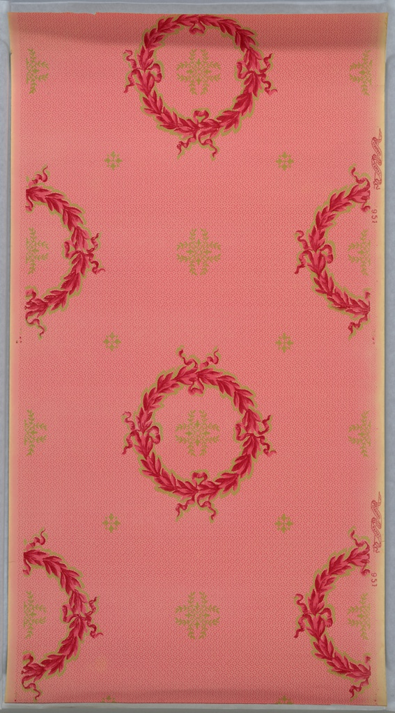 On a pink ground, dark pink ribbon wreaths containing vine motifs in greenish gold.