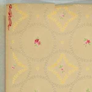 """White mica lag and feather wreaths with either small floral bouquets or yellow lag and feather diamonds in center. Between wreaths is a simplified floral motif. Beige ground. Printed in pinks, red, green, yellow and white mica. Printed in selvedge: """"Standard Papers""""."""