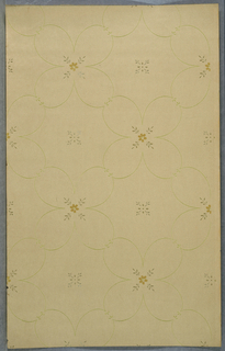 Open quatrefoils formed of foliate scrolls containing floral motif in center, forms a grid or trellis pattern with smaller floral motif in void. Printed on mica- spotted tan background.