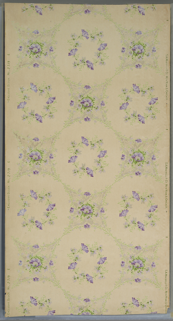 Wreaths form of purple and gray flowers on stems, encircled by a larger foliate wreath. At the intersection of these circles is a quatrefoil shape composed of more purple flowers and foliage. Printed on an off-white ground.