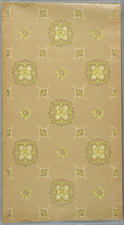 Irregular circular medallions, rather amoeba-like, with floral quatrefoil center, alternates with a diamond-shaped medallion. A round floral wreath fills the center of the grid formed by these other two medallions. Printed in shades of green, yellow, and metallic gold on tan ground.