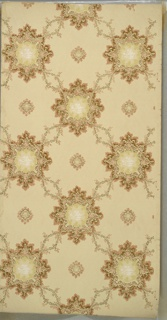 Foliate medallions connected by lag-and-feather and floral vining with fleurons in resulting negative spaces. Ground is cream. Printed in pink, brown, tan, white, and mica gold.