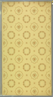 "Lines of floral wreaths alternating with lines of scroll and floral medallions. Spaces between have fleurons. Light yellow ground. Printed in grey and tan. Printed in selvedge: ""Liberty Papers"""