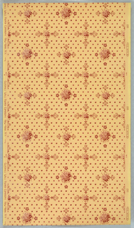 Two alternating floral motifs: small floral center with bouquet-like floral extentions on opposite sides, and a larger floral center with four single floral motifs on opposite sides. Small squares in diagonal rows cover the background. Printed in red on a yellow ground.