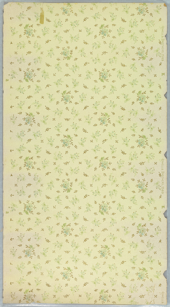 Small floral sprigs containg a single blue flower interspersed with smaller sprigs in green and metallic gold. Printed on a pale green ground.