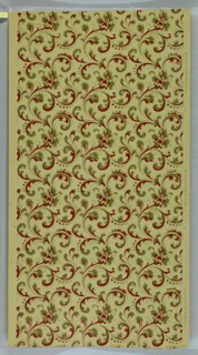 On tan paper, allover scrolls in green, red, and gold.