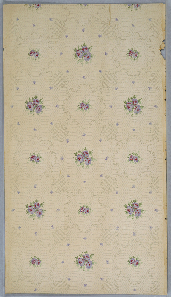Floral sprig made up of three flowers encircled by eight very petite lavender flowers, alternate with smaller sprig with two flowers. Each of the different sprigs is sepated by a scrolling framework against a honeycomb-like off-white. background.