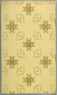 A stylized floral motif forming a quatrefoil-like design. This is centered between four ovoid foliate wreaths. Printed in brown and green on light yellow ground.