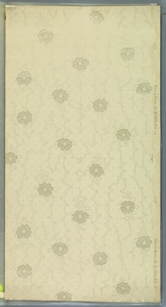 Repeating four petal flower motif with thin ribbons on moires background with staggered four dot pattern. Cream ground. Printed in white liquid mica and gold liquid mica.