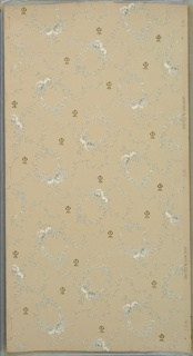 Floral wreaths connected by foliate vines interspersed with small floral ornament. Background of square dots. Beige ground. Printed in grey, white and metallic gold.