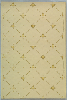 Trelllis or grid pattern with the lines formed by little boxes or squares. A cross or quatrefoil motif appears at the intersection of lines. Printed in tan, yellow, and metallic gold on a honeycomb-patterned tan background.