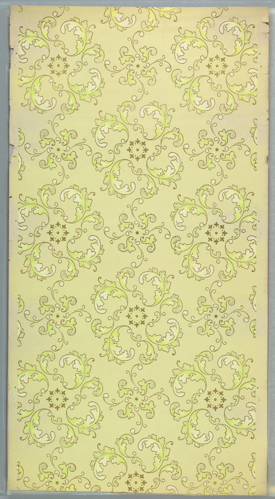 Circular medallions composed of scrolling acanthus foliage with petite metallic gold floral centers alternates with a smaller scrolling motif. Printed in green, white mica, and metallic gold on light yellow ground.