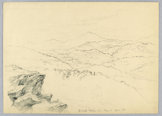 Rock ledge at left. Wooded ridges and valleys, below, with high mountain in distance, center.