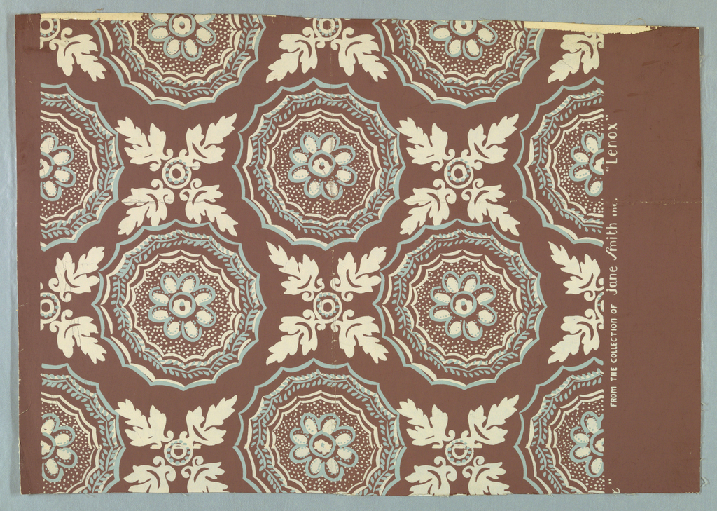 Design of two motifs arranged in rows; eight-petaled flowers surrounded by dots, leaves and scalloped lines and four leaves radiating from a center of circular lines and dots. Printed in blue and white on brown ground.