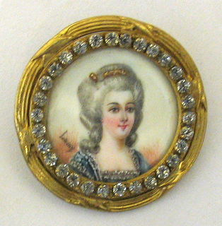 circular, with gilded metal ridged frame, with diamond-look pastes surrounding a portrait miniature in ca 1770 style