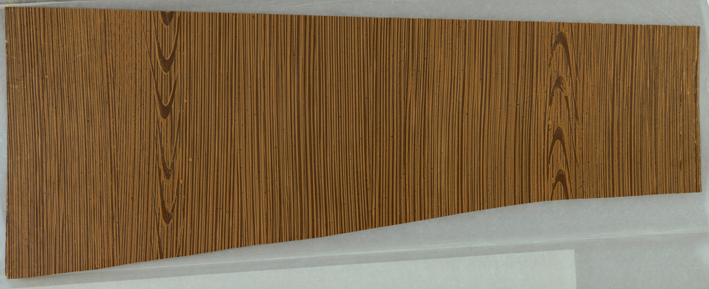Yellowish brown raised graining on dark brown ground. Imitation knot holes.