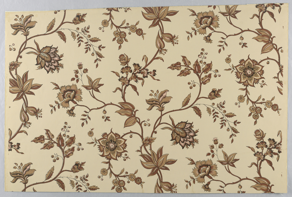 A reproduction of a wallpaper printed in France by Desfosse et Karth. The design is derived from 18th century printed cottons from India. It is an asymmetrical all-over design of continuous vines suggesting tree of life with floral sprays branching from both sides. Printed in shades of warm brown and peach on light tan ground.